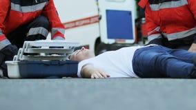 Αρσενικός ασθενής αποταμίευσης πληρωμάτων ασθενοφόρων που βρίσκεται στο δρόμο, dropper καθιέρωσης γιατρών απόθεμα βίντεο