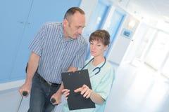 Αρσενικός ασθενής με χυτός και νοσοκόμα στο διάδρομο νοσοκομείων στοκ φωτογραφία με δικαίωμα ελεύθερης χρήσης