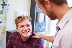Αρσενικός ασθενής που καθησυχάζεται από το γιατρό στο δωμάτιο νοσοκομείων στοκ φωτογραφία με δικαίωμα ελεύθερης χρήσης