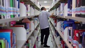 Αρσενικός ασιατικός σπουδαστής που επιδιώκει το βιβλίο στη βιβλιοθήκη απόθεμα βίντεο
