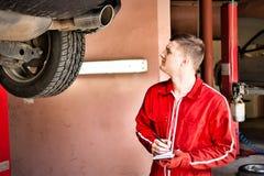 Αρσενικός αυτόματος μηχανικός που στέκεται κάνοντας τις σημειώσεις κάτω από ένα ανυψωμένο αυτοκίνητο Στοκ φωτογραφίες με δικαίωμα ελεύθερης χρήσης