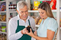 Αρσενικός βοηθώντας πελάτης ιδιοκτητών στην επιλογή του προϊόντος Στοκ Εικόνες