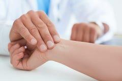 Αρσενικός γιατρός ή οικότροφος που μετρά τον υπομονετικό σφυγμό Ετήσιος σφυγμός μέτρου ελέγχου Ακριβώς παραδίδει τον πίνακα στοκ φωτογραφίες με δικαίωμα ελεύθερης χρήσης