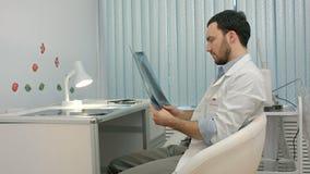 Αρσενικός γιατρός ή οδοντίατρος που εξετάζει την ακτίνα X απόθεμα βίντεο