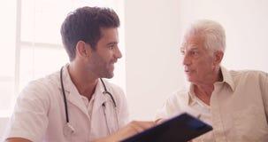 Αρσενικός γιατρός και ανώτερο άτομο που αλληλεπιδρούν το ένα με το άλλο φιλμ μικρού μήκους