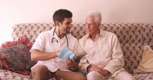 Αρσενικός γιατρός και ανώτερο άτομο που διαβάζουν ένα βιβλίο φιλμ μικρού μήκους