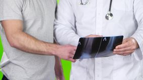 Αρσενικός γιατρός και υπομονετικό roentgenogram συζήτησης ατόμων πράσινη οθόνη απόθεμα βίντεο