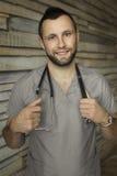 Αρσενικός γιατρός με ένα άκουσμα στηθοσκοπίων, που απομονώνεται στο καφετί ξύλο Στοκ Εικόνα