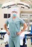 Αρσενικός γιατρός με τα χέρια στα ισχία στο δωμάτιο λειτουργίας Στοκ φωτογραφία με δικαίωμα ελεύθερης χρήσης