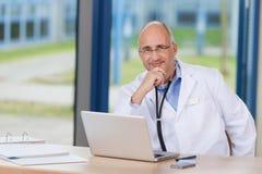 Αρσενικός γιατρός με το χέρι στο πηγούνι και το lap-top στο γραφείο Στοκ φωτογραφία με δικαίωμα ελεύθερης χρήσης