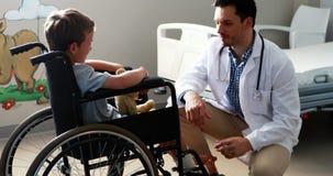Αρσενικός γιατρός που αλληλεπιδρά με τον ασθενή παιδιών στο θάλαμο απόθεμα βίντεο