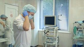 Αρσενικός γιατρός που βάζει το χειρουργικό καπέλο επάνω ενώ η νοσοκόμα που πλένει την παραδίδει ένα δωμάτιο χειρουργικών επεμβάσε Στοκ φωτογραφία με δικαίωμα ελεύθερης χρήσης