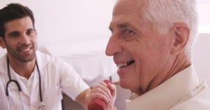 Αρσενικός γιατρός που βοηθά το ανώτερο άτομο στην άσκηση απόθεμα βίντεο