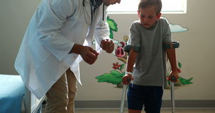 Αρσενικός γιατρός που βοηθά το τραυματισμένο αγόρι για να περπατήσει με τα δεκανίκια απόθεμα βίντεο