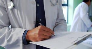 Αρσενικός γιατρός που γράφει στην περιοχή αποκομμάτων στο θάλαμο 4k απόθεμα βίντεο