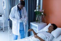 Αρσενικός γιατρός που εγχέει την έγχυση στη θηλυκή ενδοφλέβια σταλαγματιά ασθενών στο θάλαμο στοκ εικόνες με δικαίωμα ελεύθερης χρήσης