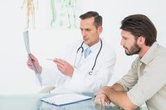 Αρσενικός γιατρός που εξηγεί την ακτίνα X σπονδυλικών στηλών στον ασθενή Στοκ Εικόνα