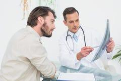 Αρσενικός γιατρός που εξηγεί την ακτίνα X σπονδυλικών στηλών στον ασθενή Στοκ Εικόνες