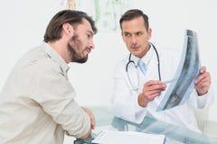 Αρσενικός γιατρός που εξηγεί την ακτίνα X σπονδυλικών στηλών στον ασθενή Στοκ φωτογραφίες με δικαίωμα ελεύθερης χρήσης