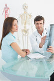 Αρσενικός γιατρός που εξηγεί την ακτίνα X σπονδυλικών στηλών στο θηλυκό ασθενή Στοκ Εικόνες
