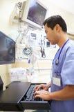 Αρσενικός γιατρός που εργάζεται στη εντατική Στοκ Εικόνες
