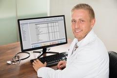 Αρσενικός γιατρός που εργάζεται στον υπολογιστή Στοκ Εικόνες