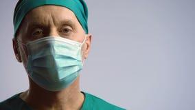 Αρσενικός γιατρός που κοιτάζει στη κάμερα σοβαρά, εμπιστοσύνη στην κλινική, ιατρική ασφάλεια απόθεμα βίντεο