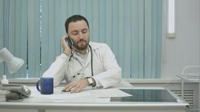 Αρσενικός γιατρός που μιλά στο κινητό τηλέφωνο στο σύγχρονο νοσοκομείο στο εσωτερικό Στοκ Εικόνα