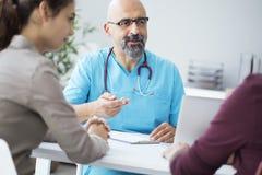 Αρσενικός γιατρός που μιλά στο νέο ζεύγος στοκ εικόνα