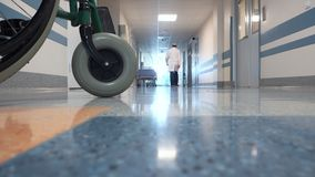 Αρσενικός γιατρός που περπατά μέσω του μακριού διαδρόμου στο νοσοκομείο φιλμ μικρού μήκους