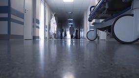 Αρσενικός γιατρός που περπατά μέσω του μακριού διαδρόμου φιλμ μικρού μήκους