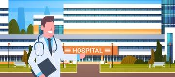 Αρσενικός γιατρός που στέκεται πέρα από το νοσοκομείο που στηρίζεται το εξωτερικό χέρι σημείου στη σύγχρονη κλινική ελεύθερη απεικόνιση δικαιώματος