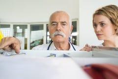 Αρσενικός γιατρός που στέκεται στα μπροστινά ράφια στο φαρμακείο στοκ φωτογραφία με δικαίωμα ελεύθερης χρήσης