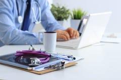 Αρσενικός γιατρός που χρησιμοποιεί ένα lap-top, που κάθεται στο γραφείο του Στοκ εικόνες με δικαίωμα ελεύθερης χρήσης