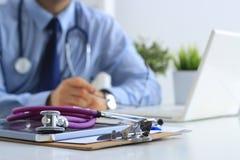 Αρσενικός γιατρός που χρησιμοποιεί ένα lap-top, που κάθεται στο γραφείο του Στοκ Φωτογραφία