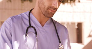 Αρσενικός γιατρός που χρησιμοποιεί την ψηφιακή ταμπλέτα στο κατώφλι φιλμ μικρού μήκους