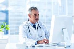 Αρσενικός γιατρός που χρησιμοποιεί τον υπολογιστή στο νοσοκομείο Στοκ εικόνες με δικαίωμα ελεύθερης χρήσης