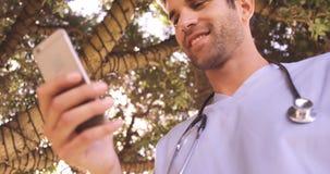 Αρσενικός γιατρός που χρησιμοποιεί το κινητό τηλέφωνο στο κατώφλι απόθεμα βίντεο
