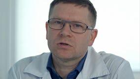 Αρσενικός γιατρός στα γυαλιά που μιλούν στη κάμερα Στοκ Φωτογραφίες