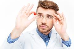 Αρσενικός γιατρός στα γυαλιά που κοιτάζει στο χάπι Στοκ φωτογραφία με δικαίωμα ελεύθερης χρήσης