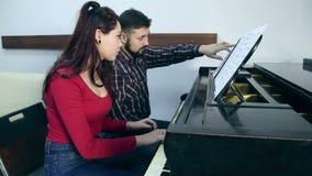 Αρσενικός δάσκαλος με το πιάνο παιχνιδιού σπουδαστών νέων κοριτσιών στο μουσικό σχολείο απόθεμα βίντεο
