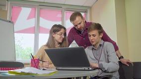 Αρσενικός δάσκαλος που βοηθά τους εφηβικούς σπουδαστές του με ένα πρόγραμμα στο σχολείο απόθεμα βίντεο