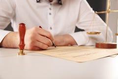 Αρσενικός δικηγόρος που εργάζεται με τα έγγραφα συμβάσεων στοκ φωτογραφία