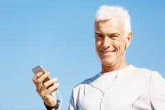 Αρσενικός δρομέας με το κινητό έξυπνο τηλέφωνό του που στέκεται υπαίθρια Στοκ εικόνα με δικαίωμα ελεύθερης χρήσης