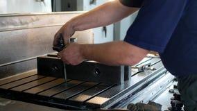 Αρσενικός ειδικός borer καθορίζει μια τροχαλία μετάλλων σε μια διευρύνοντας μηχανή, μικρή επιχείρηση, κινηματογράφηση σε πρώτο πλ απόθεμα βίντεο