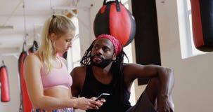Αρσενικός εκπαιδευτής και θηλυκός μπόξερ που χρησιμοποιούν το κινητό τηλέφωνο 4k φιλμ μικρού μήκους