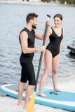 Αρσενικός εκπαιδευτικός και νέα γυναίκα που στέκονται με το paddleboard στην παραλία στοκ φωτογραφία με δικαίωμα ελεύθερης χρήσης