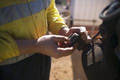 Αρσενικός επιθεωρητής χεριών τεχνικών πρόσβασης σχοινιών που αρχίζει το λουρί ασφάλειας λουριών ζωνών ποδιών πορπών επιθεώρησης στοκ φωτογραφία