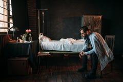 Αρσενικός επισκέπτης ενάντια στο κενό νοσοκομειακό κρεβάτι Στοκ εικόνα με δικαίωμα ελεύθερης χρήσης