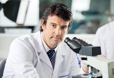 Αρσενικός επιστήμονας που χρησιμοποιεί το μικροσκόπιο στο εργαστήριο Στοκ φωτογραφία με δικαίωμα ελεύθερης χρήσης